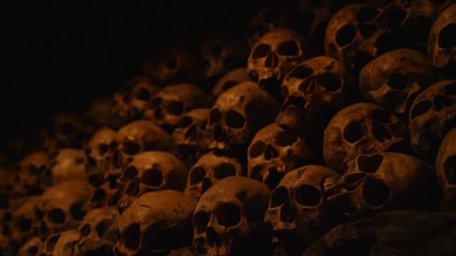 creepy panning of skull pile in dark room This spooky panning video shows a massive pile of skulls bones in a dark room. skull stock videos & royalty-free footage
