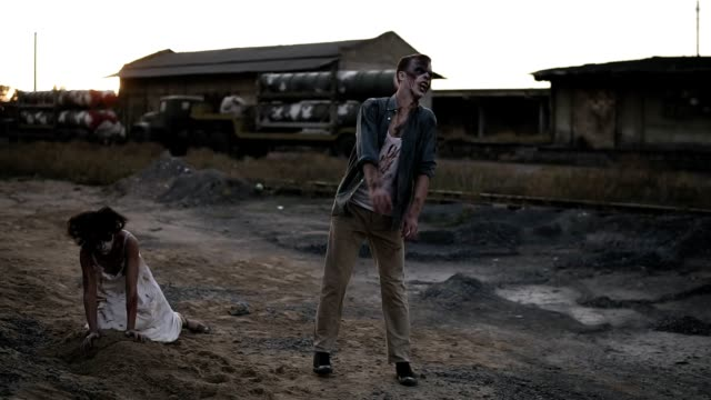 vídeos de stock e filmes b-roll de creepy two zombies in bloody clothes walking through the ruined city during the zombie apocalypse. abandoned place with trucks on the background - apocalipse