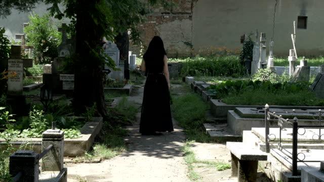 stockvideo's en b-roll-footage met griezelig vrouw lopen in begraafplaats steegje geliefde graf en plaatsen van een kroon op graf - funeral crying