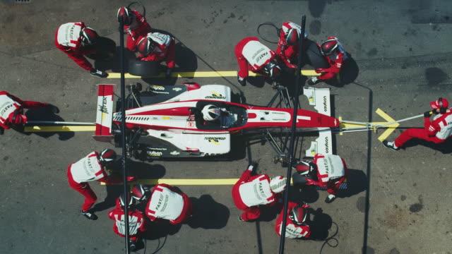 crew changing tires of racecar at pit stop - mechanik filmów i materiałów b-roll