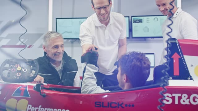 Crew congratulating driver in racecar Handheld shot of racer removing steering wheel and balaclava. Crew congratulating driver in racecar. They are at pit stop. mid adult men stock videos & royalty-free footage