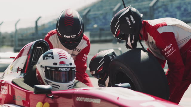 Crew members replacing tire of racecar at pit stop Crew members replacing tire of racecar during motorsport event. Technicians are repairing Formula One car at pit stop. They are at sports venue. crash helmet stock videos & royalty-free footage