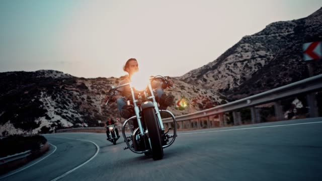 Crew of rebel motorcycle riders on mountain highway at sunset Group of rebel men riding motorcycles on mountain road at sunset during road trip motorcycle stock videos & royalty-free footage
