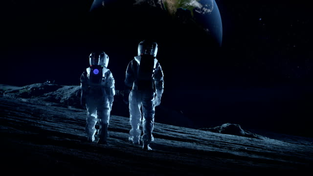 Crew of Two Astronauts in Space Suits Standing on the Moon Looking at the Beautiful Earth. High Tech Concept of Moon Colonization and Space Travel. video