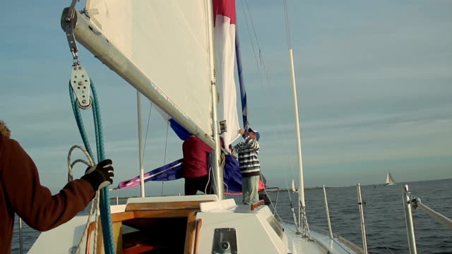 Crew raising sail on yacht, teamwork, friendship, support video