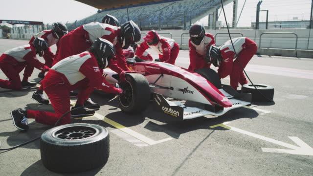 Crew repairing racecar during motorsport event