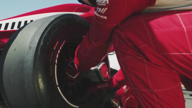 crew replacing tire of racecar at pit stop - mechanik filmów i materiałów b-roll