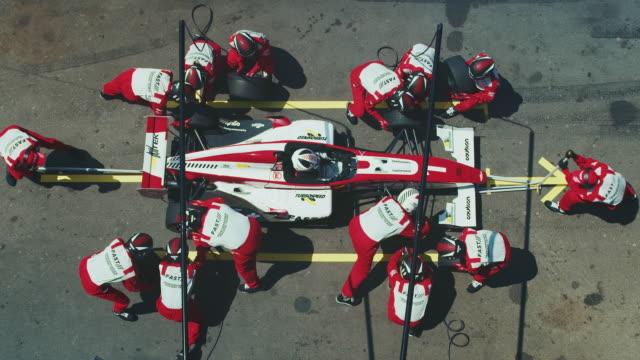 crew replacing tires of racecar at pit stop - mechanik filmów i materiałów b-roll