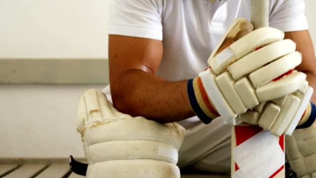 Joueur de cricket, assis sur un banc dans vestiaire - Vidéo