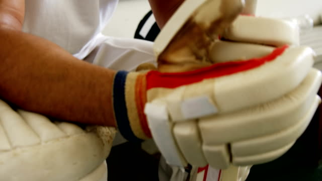 Cricket player sitting on bench in dressing room video