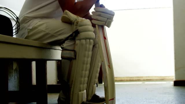 Cricketspieler sitzen auf Bank in Umkleidekabine – Video