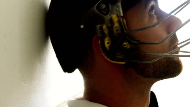 vídeos y material grabado en eventos de stock de jugador de cricket sentado con la cabeza apoyada contra la pared en vestidor - críquet