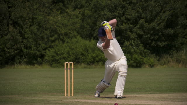 A cricketer batting drives the ball in slow motion. video