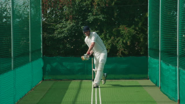 A Cricketer doing net practise hits the cricket ball. A Cricketer playing in the nets for practise or preparation hits the ball well. padding stock videos & royalty-free footage