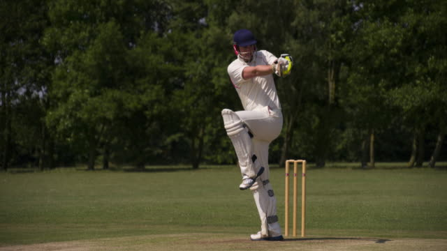 A Cricketing batsman hits the ball in slow motion. video