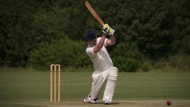vídeos y material grabado en eventos de stock de un bateador de críquet se juega un tiro en cámara lenta. - críquet