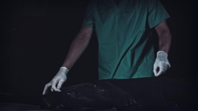 vídeos y material grabado en eventos de stock de 4k delito tanatorio funeraria abre bolsa negra con cuerpo muerto - autopsia