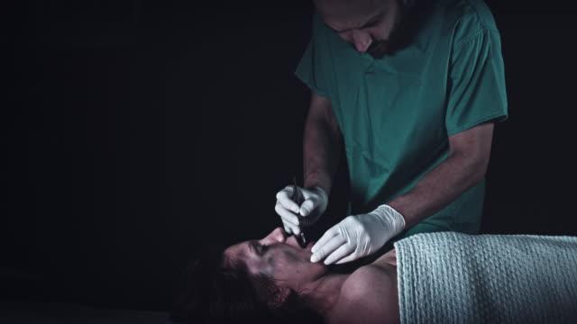 vídeos y material grabado en eventos de stock de 4 k delito tanatorio funeraria sacando de la boca del cadáver - autopsia
