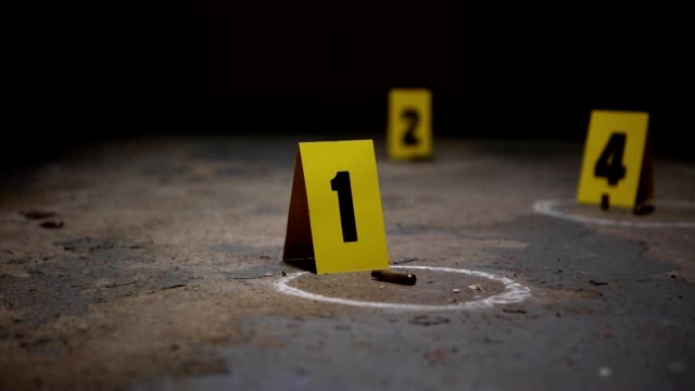 Crime Scene Markers Wide pan of crime scene markers of bullet casings on a concrete floor crime scene stock videos & royalty-free footage