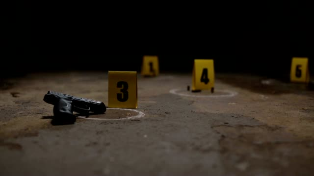 Crime Scene Markers Wide pan of crime scene markers of a gun and bullet casings on a concrete floor crime scene stock videos & royalty-free footage