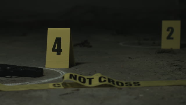 Crime Scene Wide pan of crime scene of discarded gun and bullet casings with torn down crime scene tape crime scene stock videos & royalty-free footage