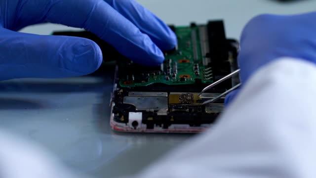уголовный эксперт удаления микроборда из сожгли мобильный телефон, расследование - expert стоковые видео и кадры b-roll