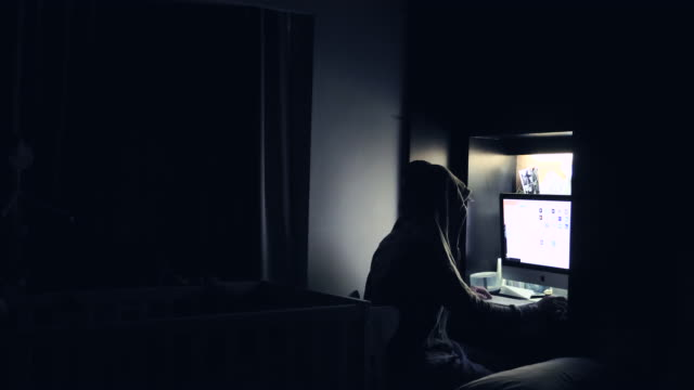 Criminal Hacker cracking system, Computer Terrorism, Young male hacker in hoodie sweater working on a computer in a dark office room. Bangkok, Thailand. hacker stock videos & royalty-free footage