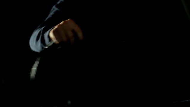 vídeos de stock e filmes b-roll de criminal in black mask stealing drug packages from automobile trunk, robbery - roubar crime