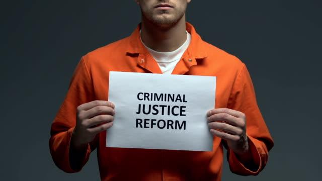 criminal justice reform phrase on cardboard in hands of caucasian prisoner - wine filmów i materiałów b-roll