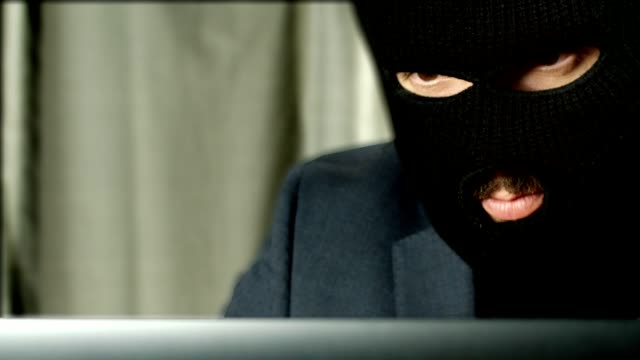 A Criminal Looking At A Laptop With A Serious Expression video