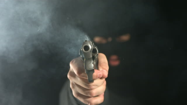 stockvideo's en b-roll-footage met criminal shoots gun directly at camera, slow motion - gun shooting