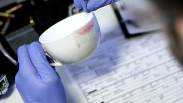 Criminal specialist taking lipstick print from white cup from murder scene video