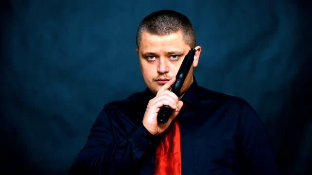 en kriminell med en pistol. skylten är tyst. blå bakgrund. - hotelse bildbanksvideor och videomaterial från bakom kulisserna
