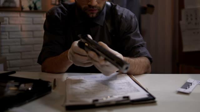 Criminalist examining gun from murder scene, working on case in police station video