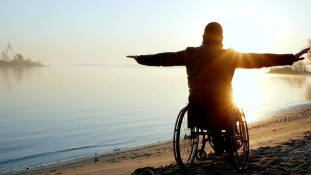 cripple on wheel chair, hands up, sundown, lonely disabled on video