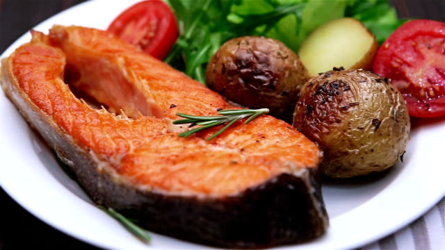 Crispy roasted salmon steak Crispy roasted salmon steak Isolated on wooden background cooked stock videos & royalty-free footage
