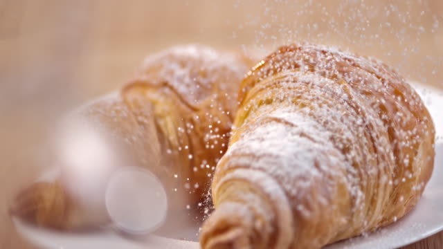 slo mo croissants being sprinkled with sugar - french food stock videos and b-roll footage