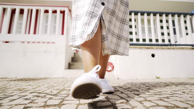 vídeos de stock e filmes b-roll de crop legs in white sneakers on street costa nova - aveiro