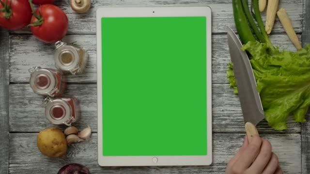 crop person examining knife near tablet - tavolo legno video stock e b–roll