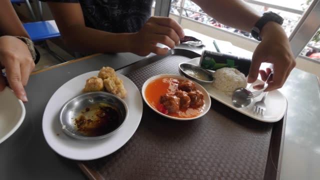 vidéos et rushes de la vue de culture de la main d'un homme et d'une femme prépare des nourritures sur la table dans un café. - fourchette