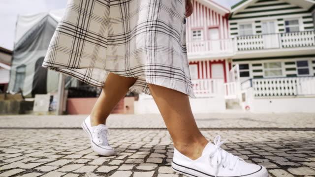 vídeos de stock e filmes b-roll de crop woman walking near colorful buildings - aveiro