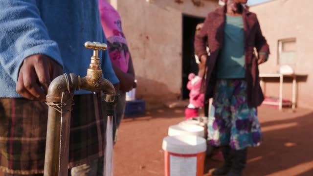 Cropped close-up of african woman opening a water tap while woman stand in line to collect water in plastic buckets Cropped close-up of african woman opening a water tap while woman stand in line to collect water in plastic buckets hungry child stock videos & royalty-free footage