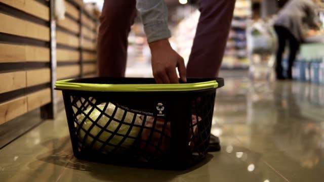 Abgeschnittene Aufnahmen eines Mannes, der gemüse im Supermarkt wählte und in der Gemüseabteilung auf den schwarzen Korb auf dem Boden legte. Untere Teile – Video