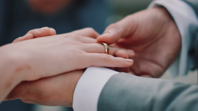 Cropped hands of couple exchanging wedding rings