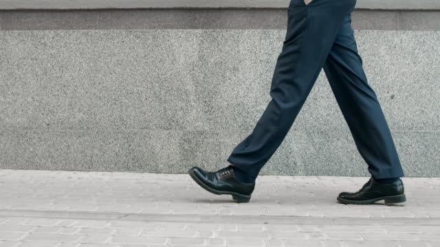 cropped image man walking in black shoes. closeup male feet going near building - fare un passo video stock e b–roll