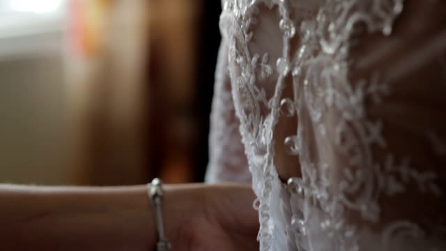 Cropped image of woman dressing up bride video
