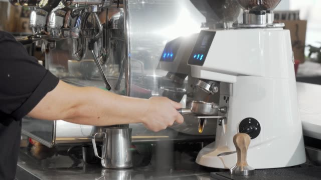 Cropped shot of a barista grinding coffee beans using coffee machine