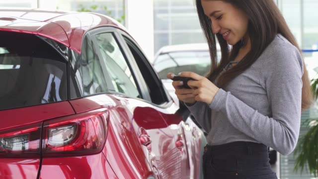 Cropped shot of a woman using her smart phone standing near her car Cropped shot of a happy beautiful woman smiling joyfully using her smart phone at the dealership showroom while choosing a new automobile. Cheerful female customer buying a new car. car shopping stock videos & royalty-free footage