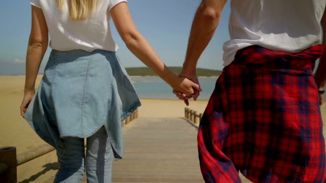 Cropped shot of couple holding hands and walking on beach