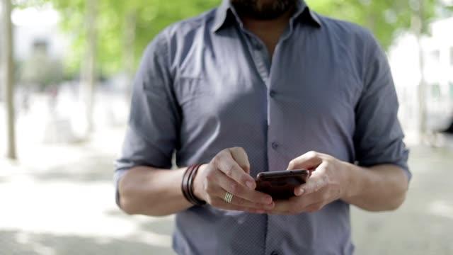 vidéos et rushes de recadrée de tir de l'homme utilisant le téléphone portable extérieur - course poursuite